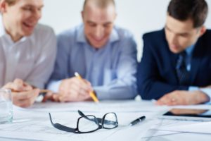 Closeup image of eyeglasses and a ballpoint on the table where business colleagues sharing the ideas on the foreground